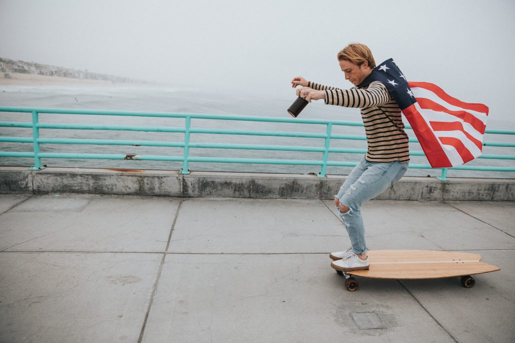 boy skateboarding with American flag cape