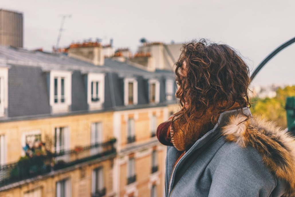 Woman looking out from balcony in Paris