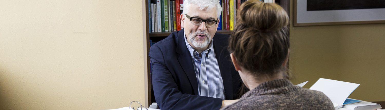 Gordon Fischer at desk with client