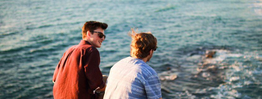 Two men having a conversation near the ocean