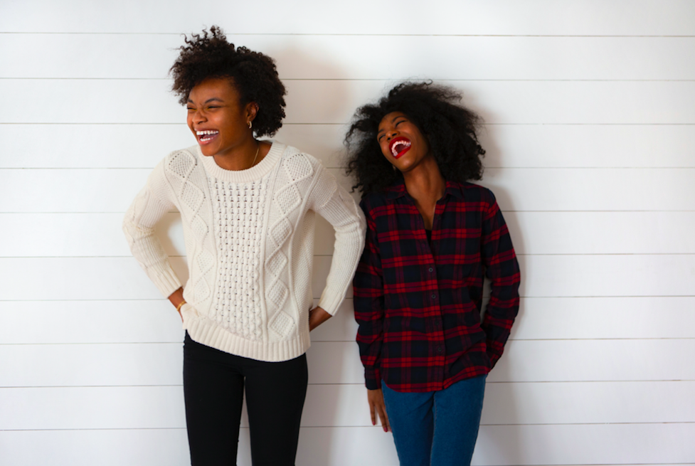 two people standing against white wall laughing