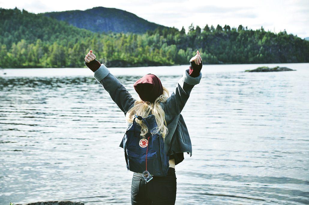 woman cheering at water's edge