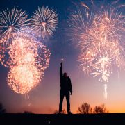 fireworks with man reaching up to the sky