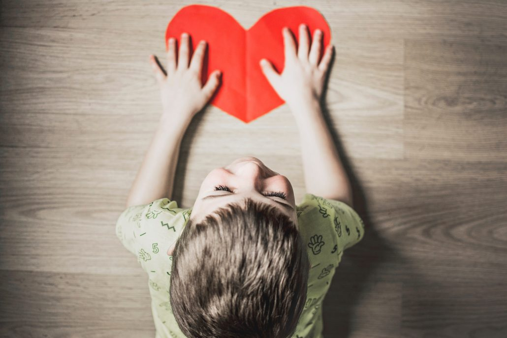 child with red heart