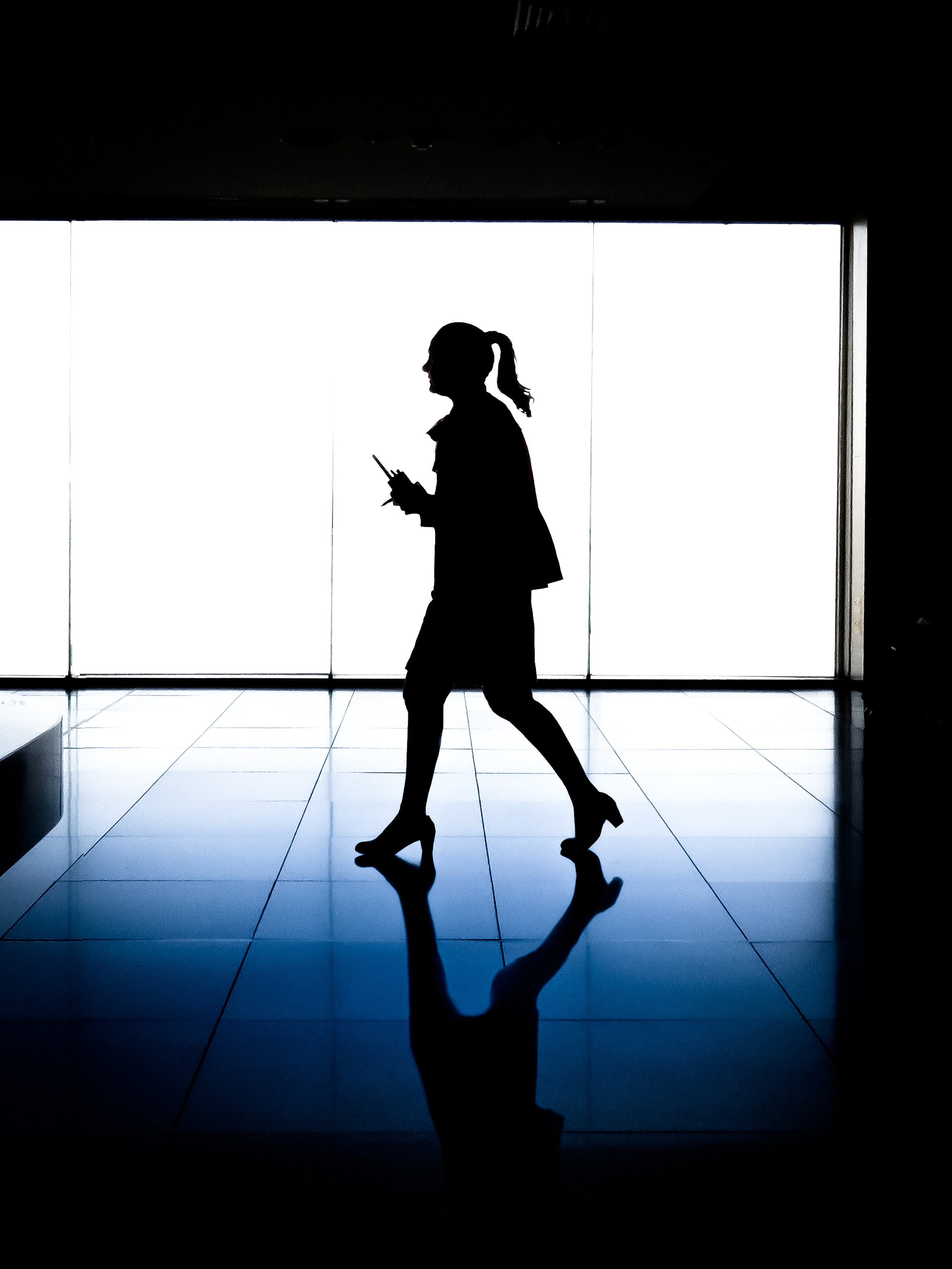 woman walking against blue window