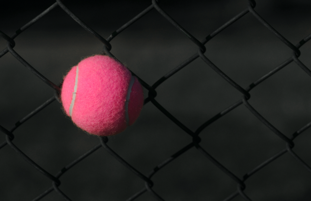 Pink tennis ball stuck in fence