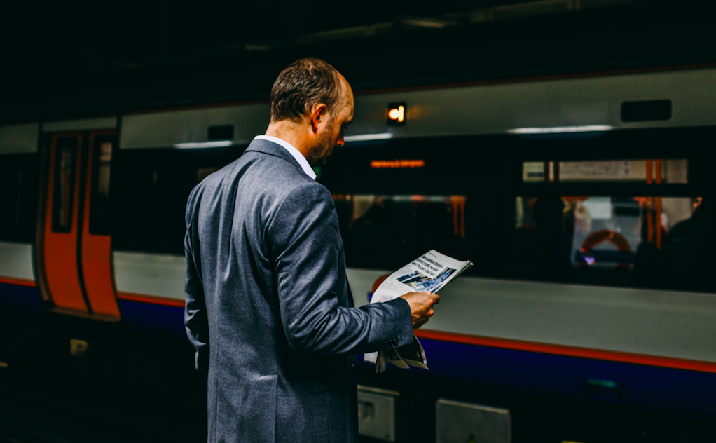 man with newspaper near train