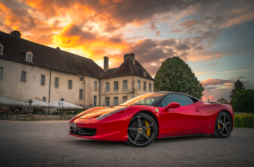 sports car in front of mansion